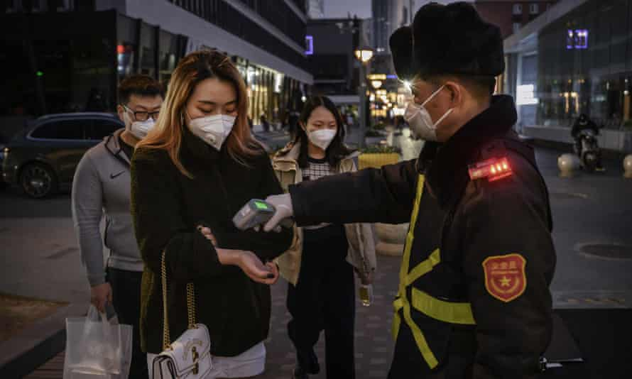 A woman in Beijing has her temperature checked before entering a shopping mall