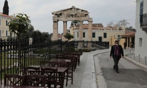 A man wearing a protective mask walks next to empty tables of a restaurant that is closed to customers as a precaution against the spread of the coronavirus (COVID-19), at the ancient Roman Agora in Athens, Greece, March 15, 2020. REUTERS/Costas Baltas