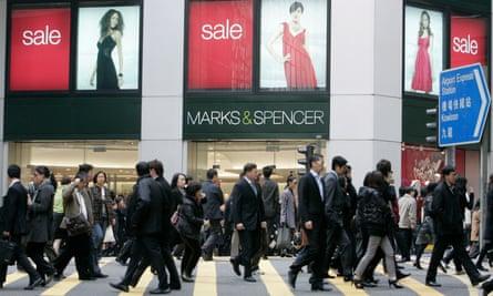 Pedestrians pass a branch of Marks & Spencer in Hong Kong