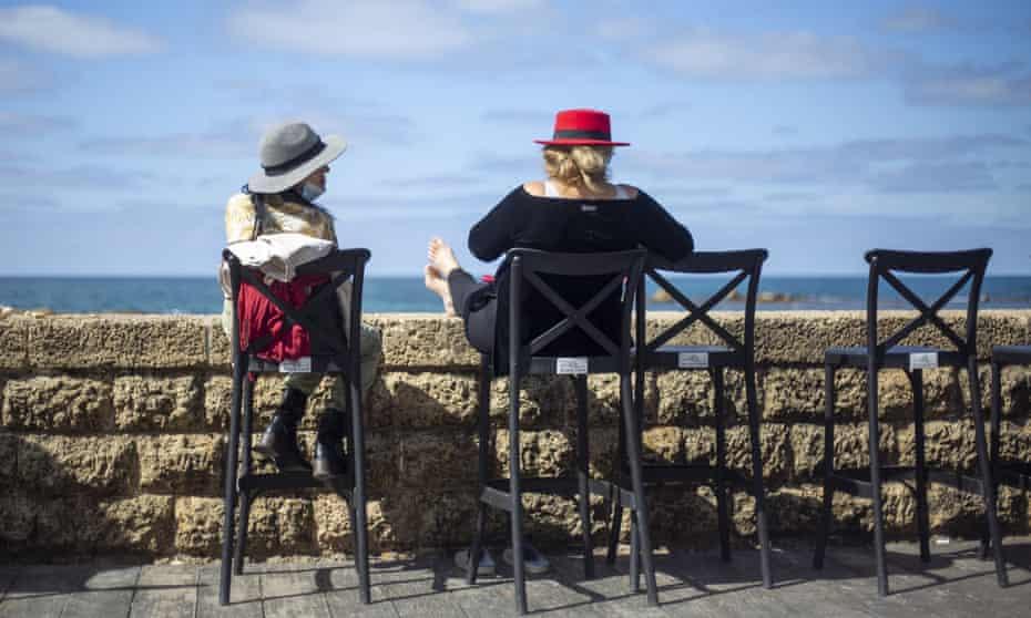 Women sit in a cafe overlooking the Mediterranean in Tel Aviv, Israel