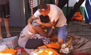 A crew member of the Open Arms humanitarian boat comforts a person rescued from the sea.