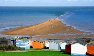 Beach huts and shingle spit at Tankerton, Kent, UK.