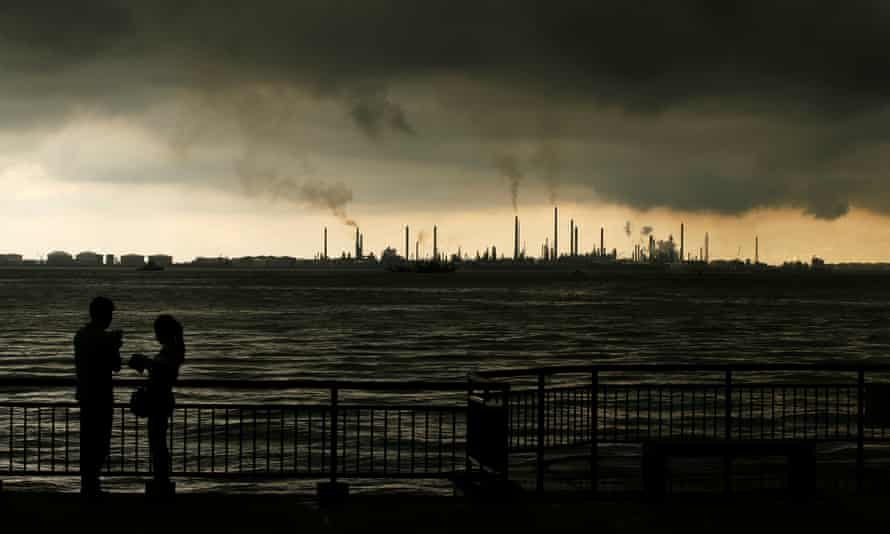 Storm clouds gather over Shell's Pulau Bukom oil refinery in Singapore.
