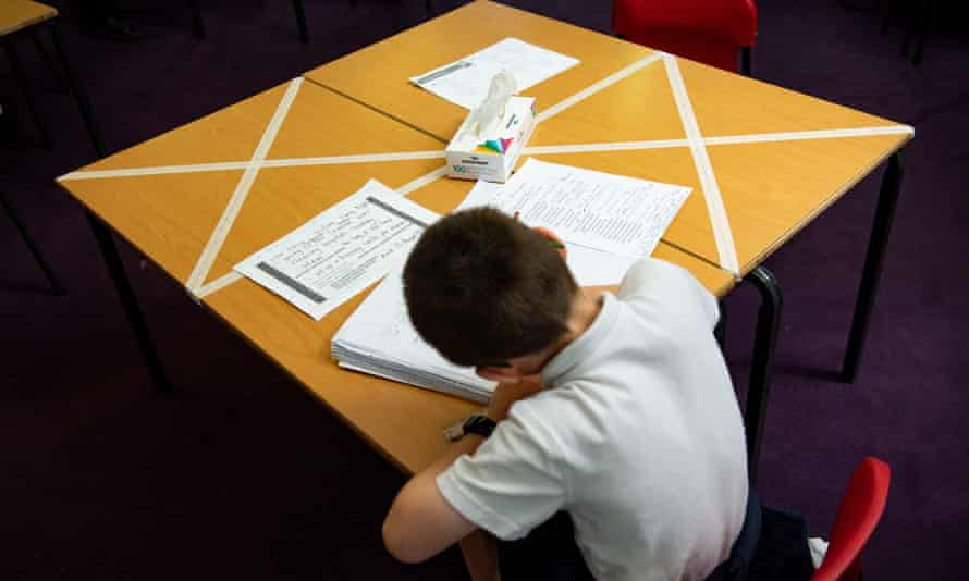 Child working at a table, with seats taped off for social distancing