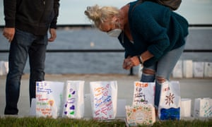 A woman places lights inside luminaries during a vigil in remembrance of victims of overdose deaths in Gloucester, Massachusetts.
