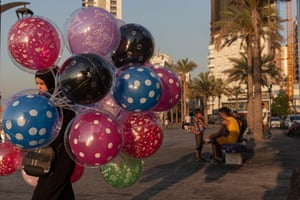 A woman sells balloons and children sell roses in Beirut, Lebanon.
