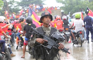 A policeman stands guard as supporters of presidential candidate Francisco Guterres ride through the street in Dili, East Timor