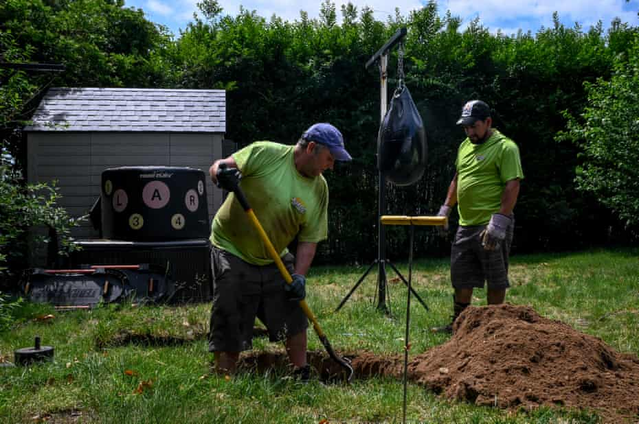 Employees at Emil Norsic and Son, Inc., Michael McCallen (left), 47, and Isidro Arellanos (right), 39, dig up a cesspool cover after receiving an emergency call from a resident experiencing sewage backup on Thursday, June 10, 2021 in the Sag Harbor village of Southampton, New York. Without a public sanitation department, residents of Southampton mainly rely on private businesses, such as Emil Norsic and Son, Inc., to handle sewage problems.
