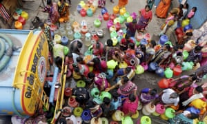 Indians queue to fill pots from a water tanker in Chennai.