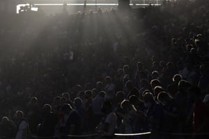 Fans are caught by the late afternoon sunlight before the match.