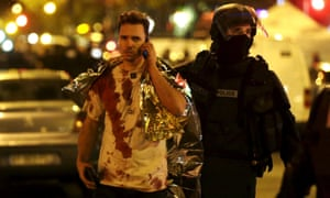 A French policeman assists a blood-covered victim near the Bataclan