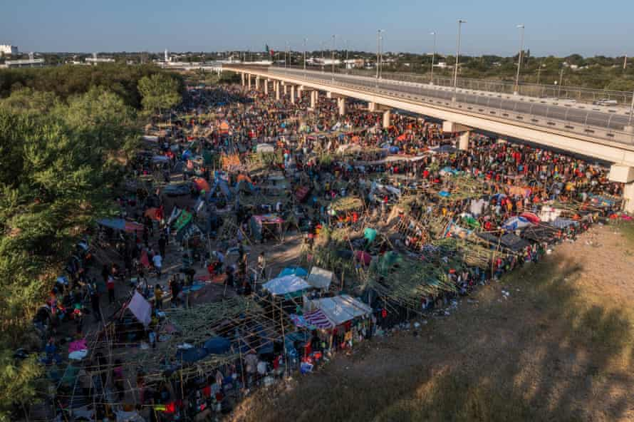 Migrants await to be processed along the Del Rio international bridge after crossing the Rio Grande river into the US on Sunday.