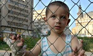 Romanian street child looks on through a fence