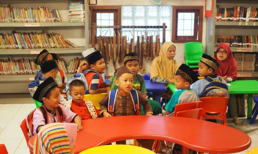 Indonesian children in a colourful classroom surrounded by bookshelves.