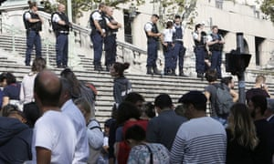 Passengers wait in front of a line of police officers blocking access to Saint-Charles in Marseille