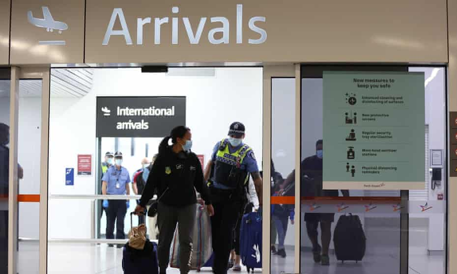 Police at Perth airport escort Qantas passengers to buses to take them to a CBD hotel for quarantining