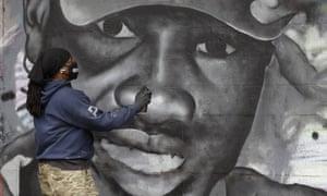 Artist Theo Ponchaveli paints a mural of Ahmaud Arbery in Dallas last week.
