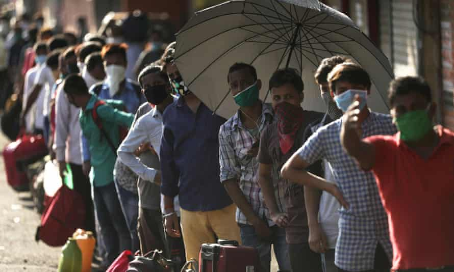People queue for transport in Mumbai, India