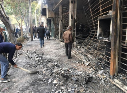 Iranians walk past a charred bank that was set ablaze during a demonstration in the central city of Isfahan.