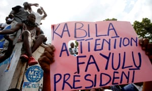 Supporters of Martin Fayulu hold a sign before a political rally in Kinshasa.