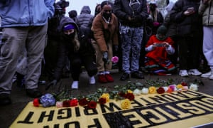 People lay flowers on a sign as they rally outside the Brooklyn Center Police Department.