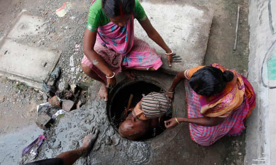 A labourer cleans an underground drain in Kolkata.