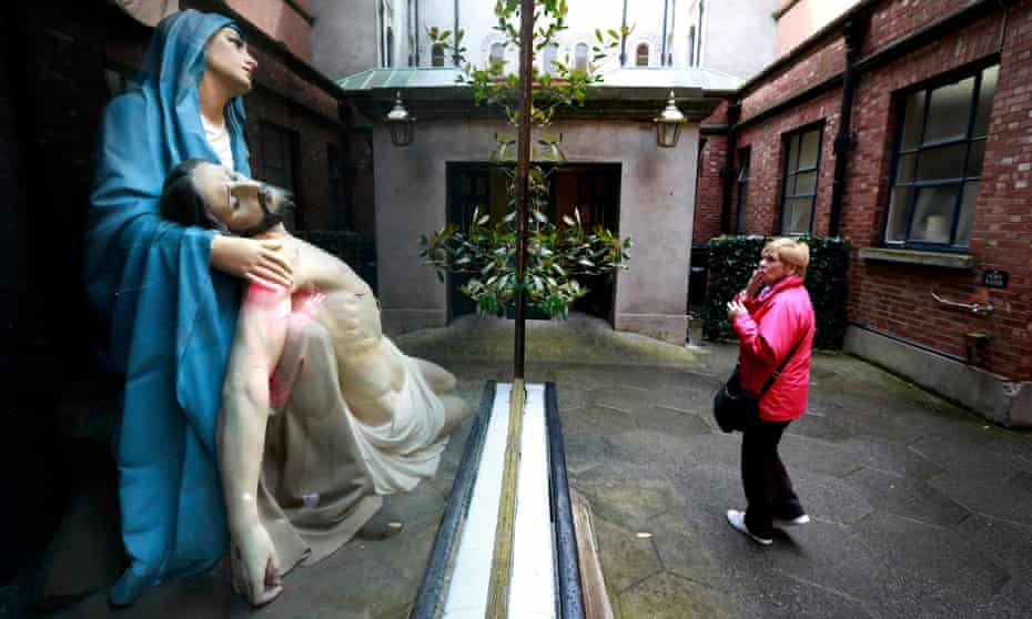 A woman prays in front of a statue of Mary and Jesus in the Grafton street area of Dublin.