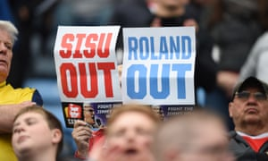 A fan holds signs protesting against both the Charlton and Coventry City owners.