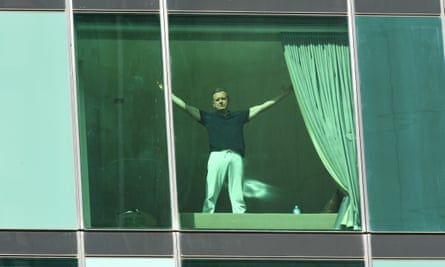 A man gestures from Melbourne hotel quarantine in March.