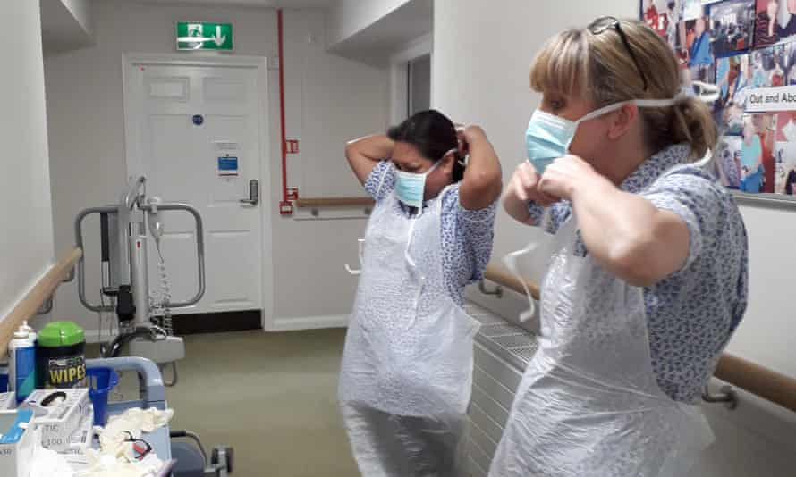 Workers put on basic face masks and aprons at a care home in Buckinghamshire.