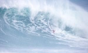 Kelly Slater focuses on a huge wave at the Eddie Aikau surf competition.