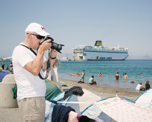 A tourist photographs camps on the beach in Kos; in the background, a ferry holds hundreds of Syrians waiting for immigration papers