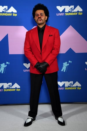 A strong red carpet look from The Weeknd: black gloves, spats, moustache and a bold red suit jacket.