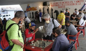Men wearing masks play chess under a bridge in Caracas, Venezuela, Saturday, Dec. 26, 2020, amid the coronavirus pandemic.
