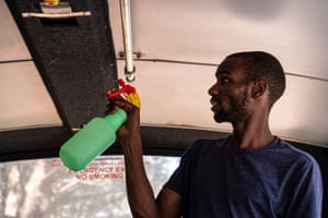 Edward, who works as a matatu conductor, cleans the seats of the bus between shifts