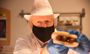 Boris Johnson holds up a roll filled with sausage during a visit to a hospital in Reading, England