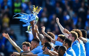"""Manchester City's players lift the Premier League trophy. Pep Guardiola said """"It's the toughest title we have won in all my career, by far."""""""