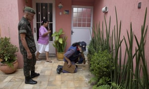 A soldier and a health agent check a residence during an operation against the <em>Aedes aegypti</em> mosquito, which is a vector for transmitting the Zika virus in São Paulo, Brazil, on 20 January.
