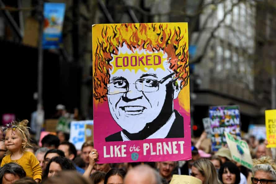 Crowds hold up placards as they march in Melbourne on 20 September as part of the global climate strike.