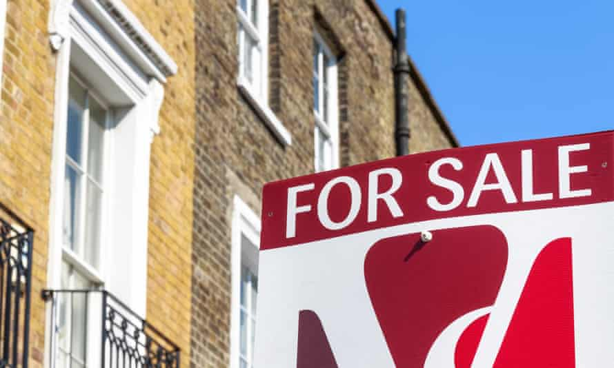 a for sale sign outside a yellow brick Victorian terrace home