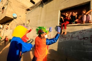 Khan Younis, Gaza Strip: A clown and a person wearing a duck costume entertain Palestinian children during lockdown