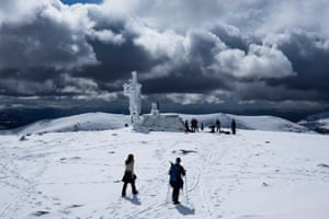 Fresh showers of snow re-coated Cairngorm summit as cross country and touring skiers pause at the summit