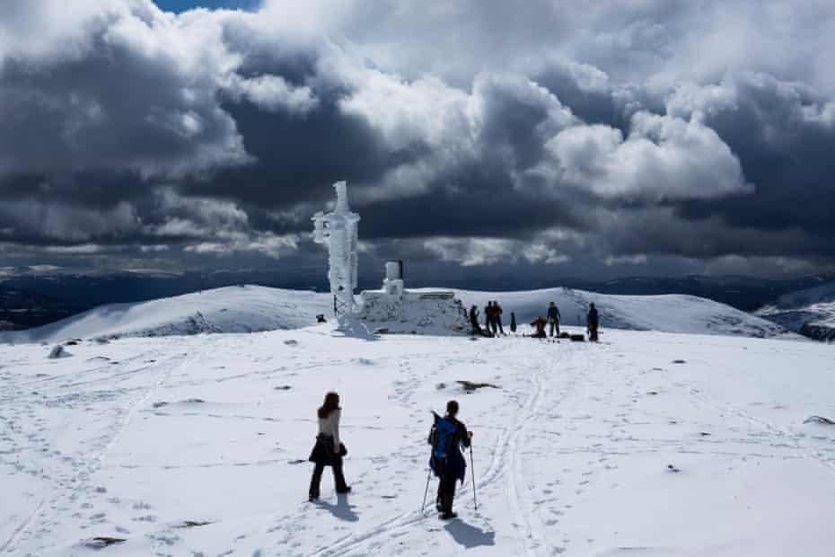 Fresh showers of snow re-coated Cairngorm summit as cross country and touring skiers pause at the summit weather station to eat lunch and prepare for the descent.