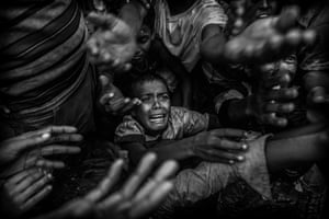 A Rohingya refugee boy cries as he fights his way in the crowd to get food aid from a local NGO at the Balukali refugee camp on 18 September in Cox's Bazar, Bangladesh, where more half a million Rohingya refugees have fled an offensive by Myanmar's military