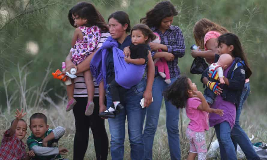 Central American immigrants await transportation to a US border patrol processing center after crossing the Rio Grande from Mexico into Texas.