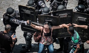 A heavily armed riot policeman squirts pepper spray into a woman protester's face