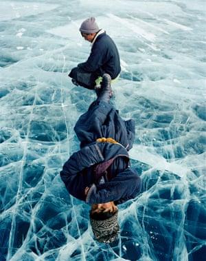 Two men lying on frozen Lake Khövsgöl