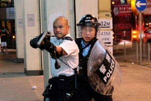 A police officer points a gun towards anti-extradition bill protesters who surrounded a police station where detained protesters are being held during clashes in Hong Kong, China July 30, 2019.