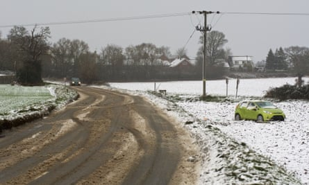 A car left in the snow next to a road in Norfolk.