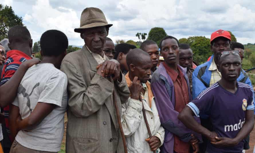 Spectators look on as Truth and Reconciliation Commission officials inspect remains at a mass grave in Mwaro, Burundi.